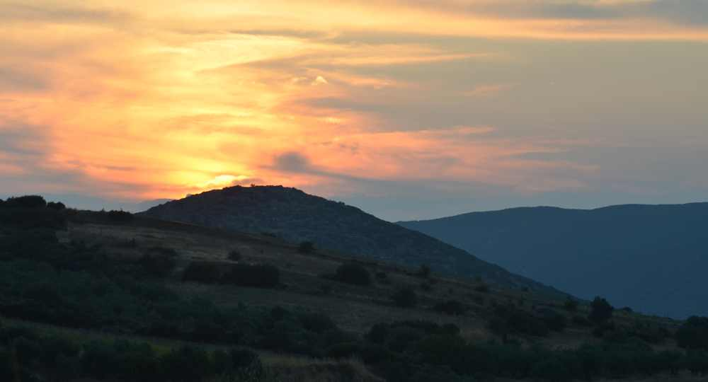 view of the sun setting from st. nicholas church, exarchos greece