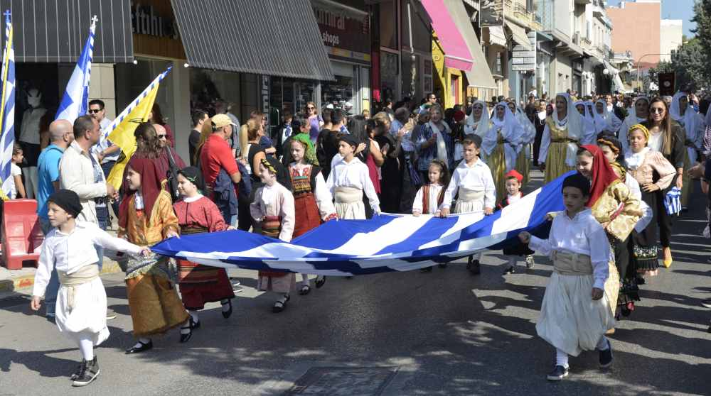 children walking with large flag of Greece during nea ionia parade for ohi day