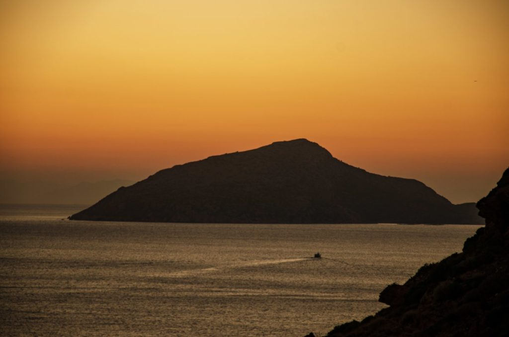 patrikos island with sunset colours in the sky behind and small boat in the sea