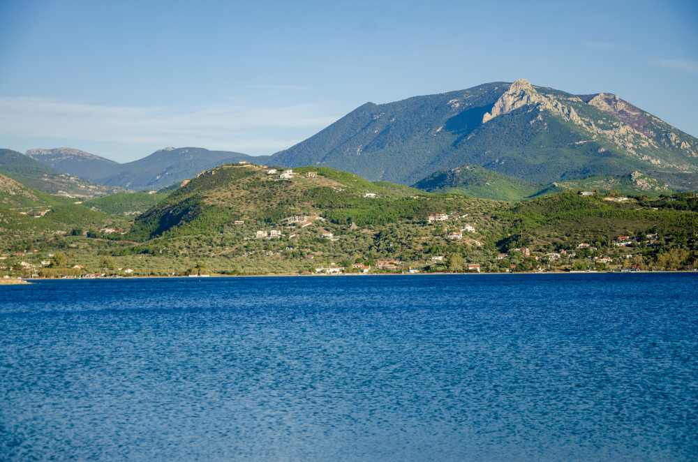 lake vouliagmenis with mountain on other side and houses