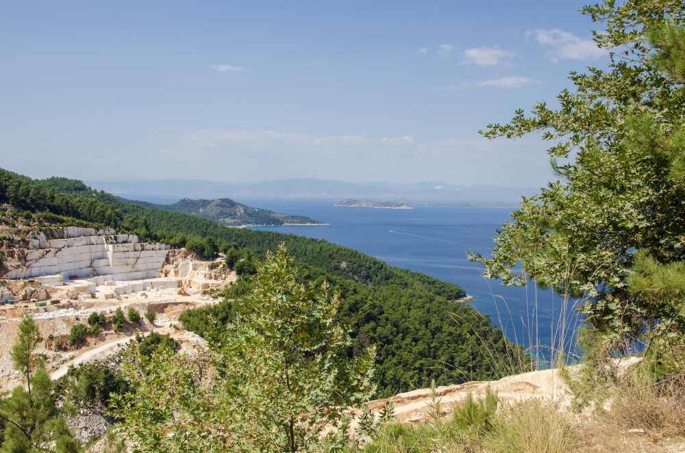 view of aegean sea above marble beach and marble quarrying